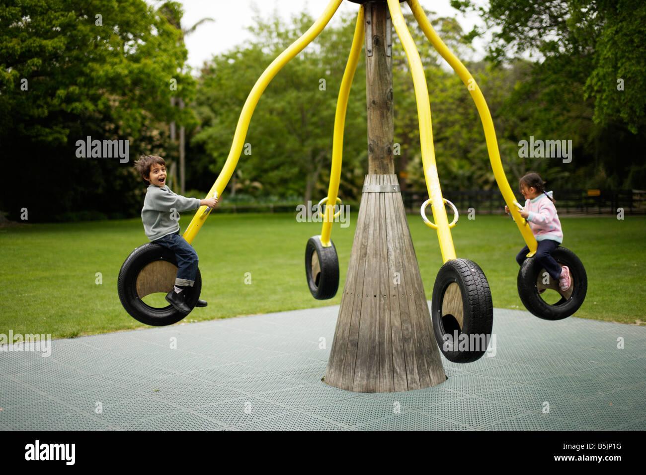 Six ans joue dans l'aire de jeux avec sa sœur, âgée de cinq ans Banque D'Images