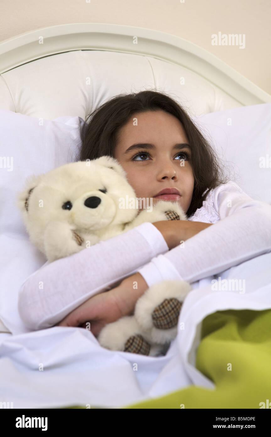 Une petite fille dans le lit avec un ours en peluche Banque D'Images
