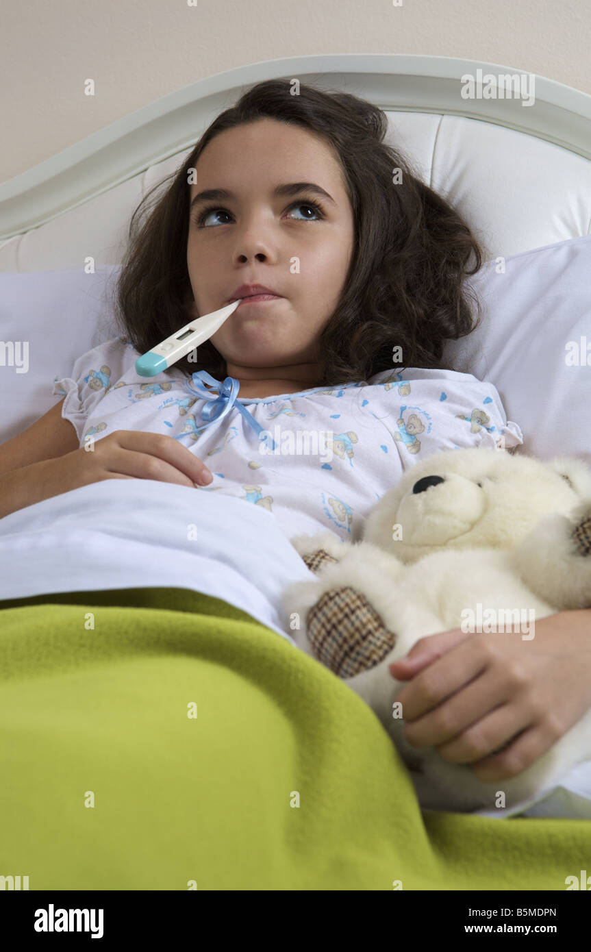 Une petite fille dans le lit de la prise de température Banque D'Images