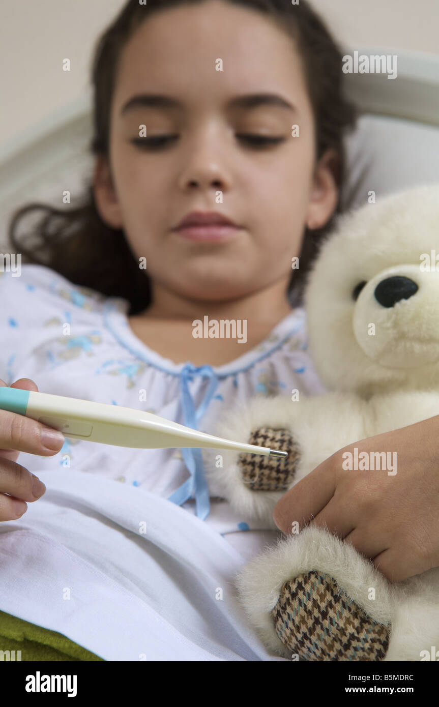 Une petite fille dans le lit à la recherche d'un thermomètre à Banque D'Images