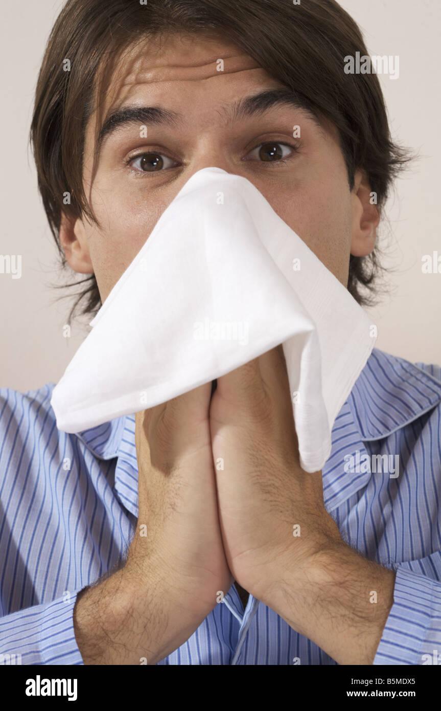 Un homme soufflant son nez Banque D'Images