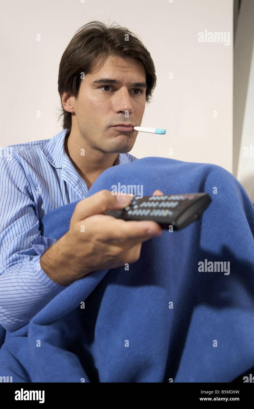 Un homme avec un thermomètre dans la bouche et la tenue d'un contrôle à distance Banque D'Images