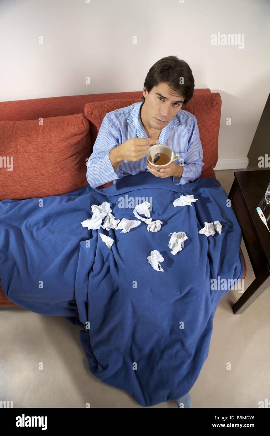 Un homme malade assis sur un canapé avec une tasse de thé Banque D'Images