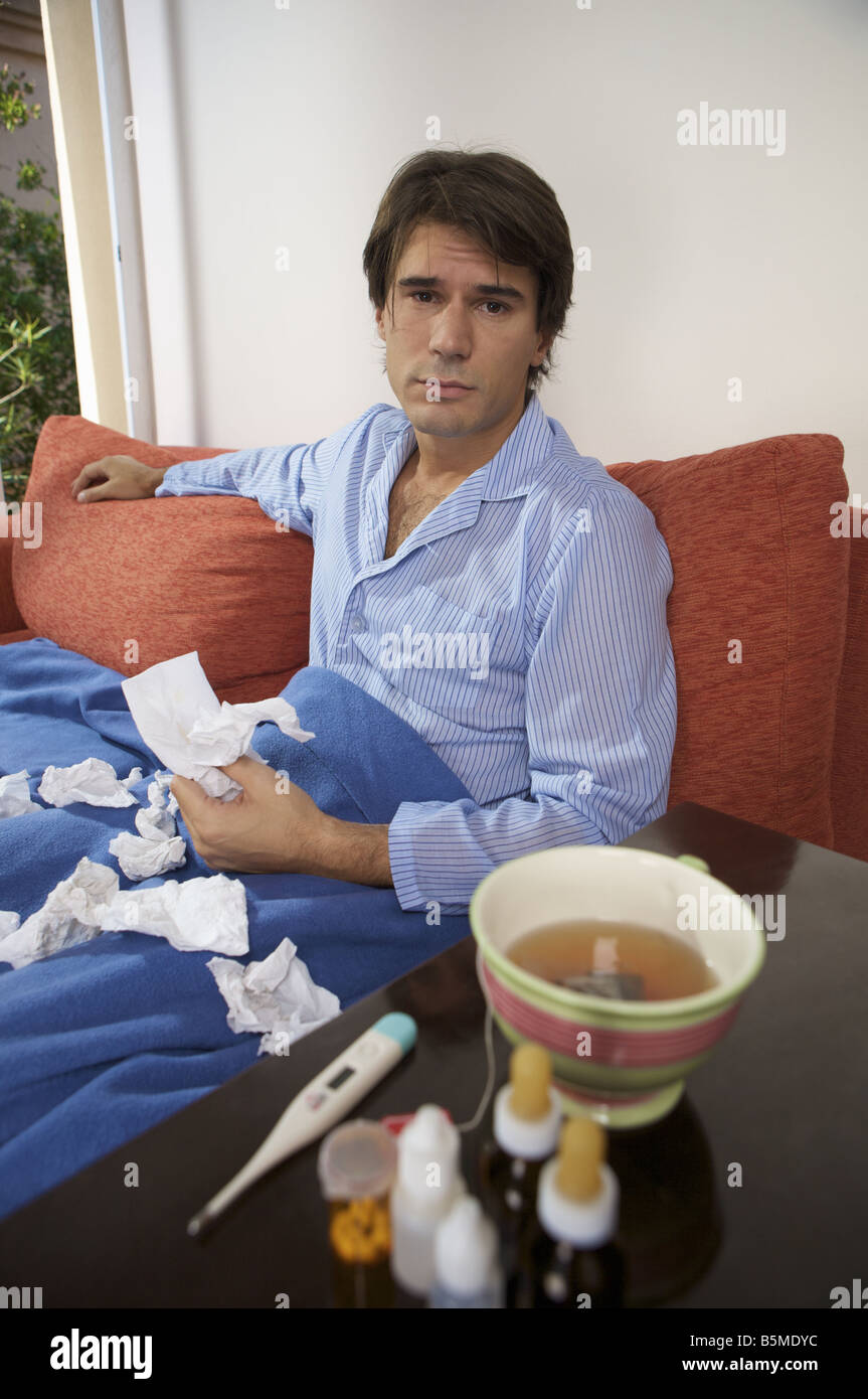 Un homme malade wearing pajamas while sitting on a couch Banque D'Images