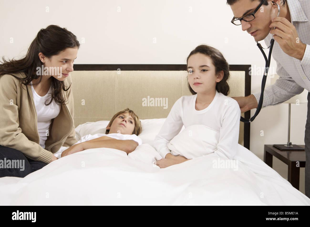 Un médecin l'examen de deux enfants au lit Banque D'Images