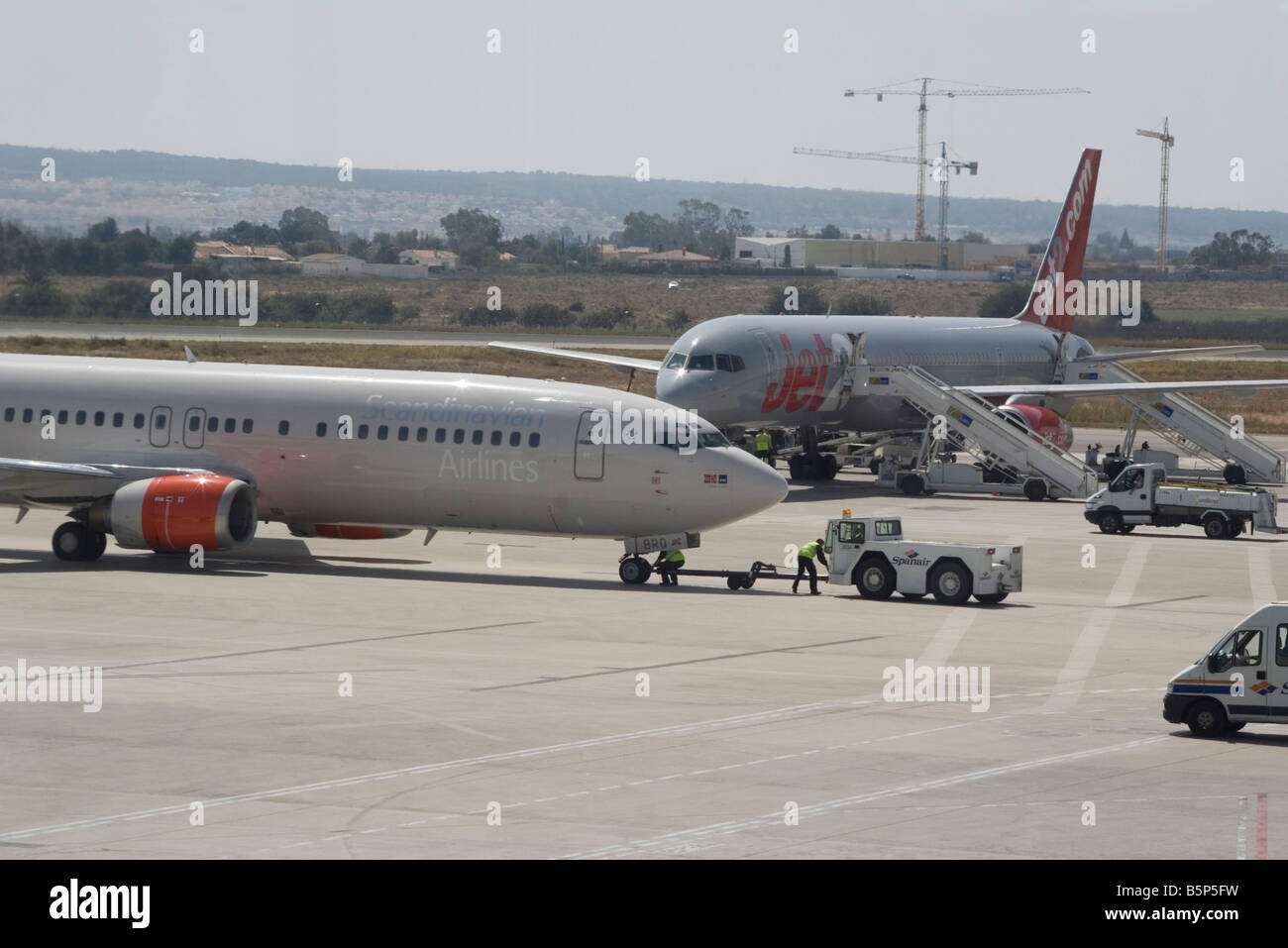 Le personnel au sol de travailler sur un avion et Scandinavian Airlines un Jet2 com avion sur le tarmac de l'aéroport Photo Stock