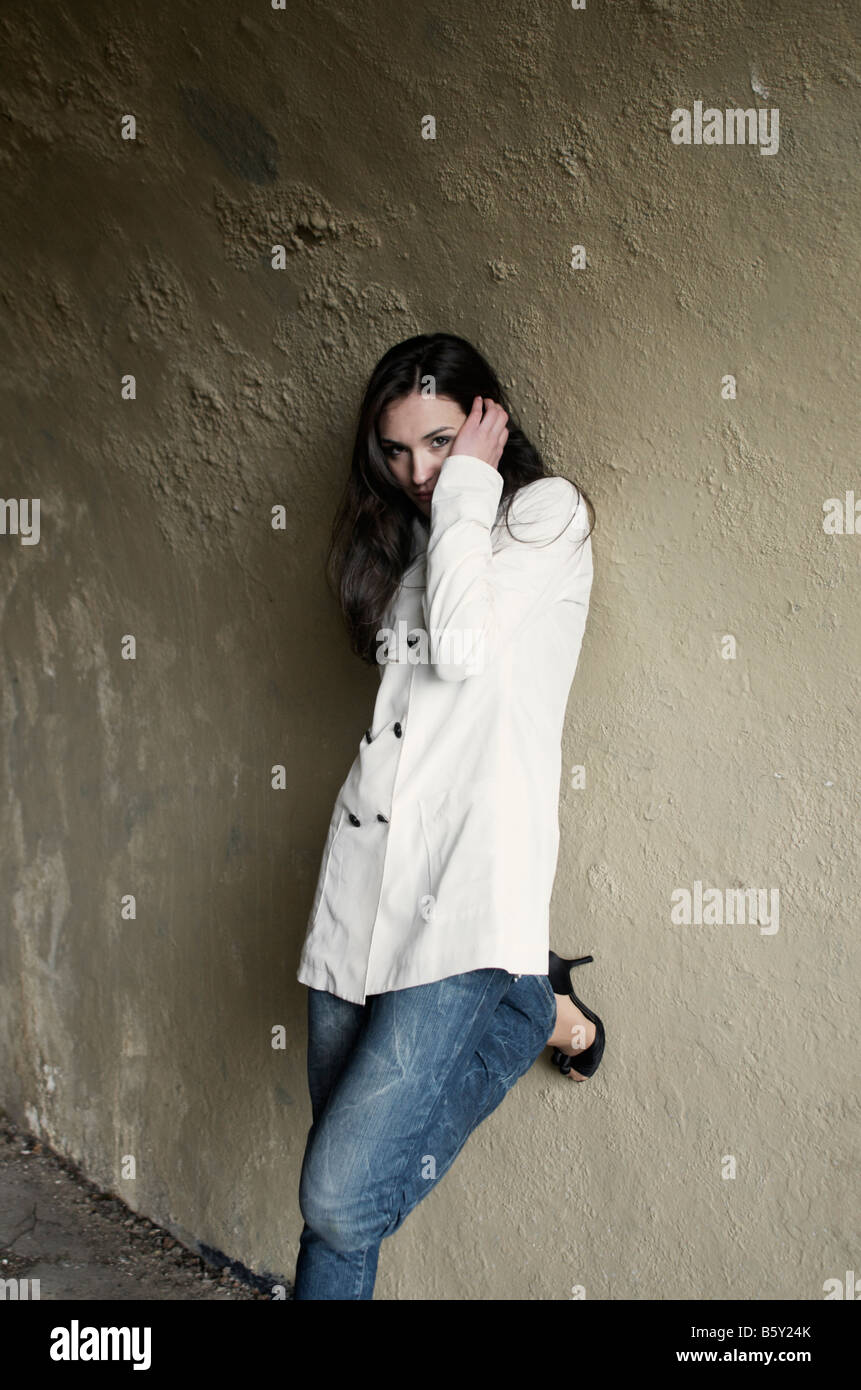 Young attractive woman leaning on the wall Photo Stock