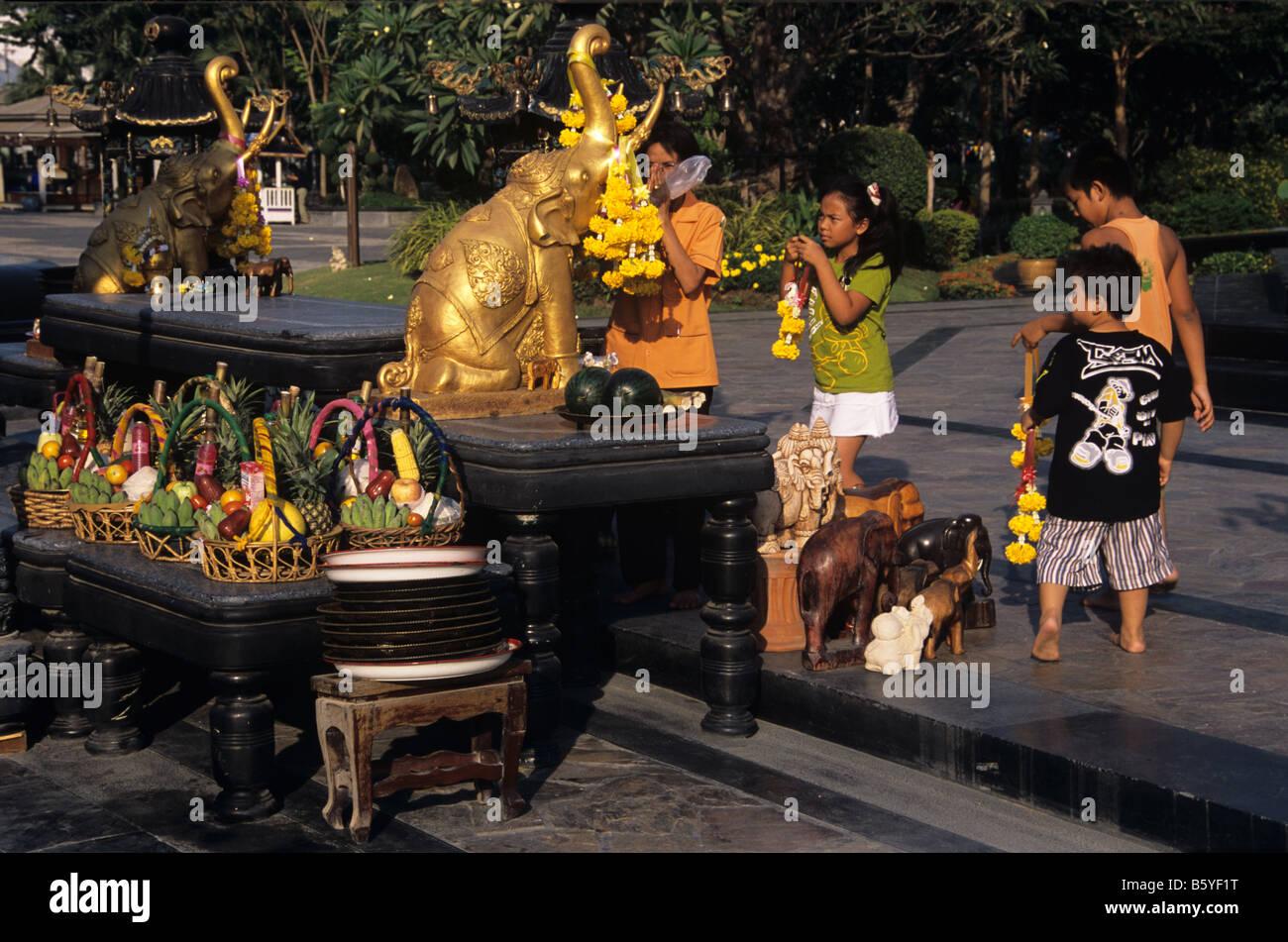 Une famille thaïlandaise prier et laisser les fruits et garland offrandes à l'éléphant à Photo Stock