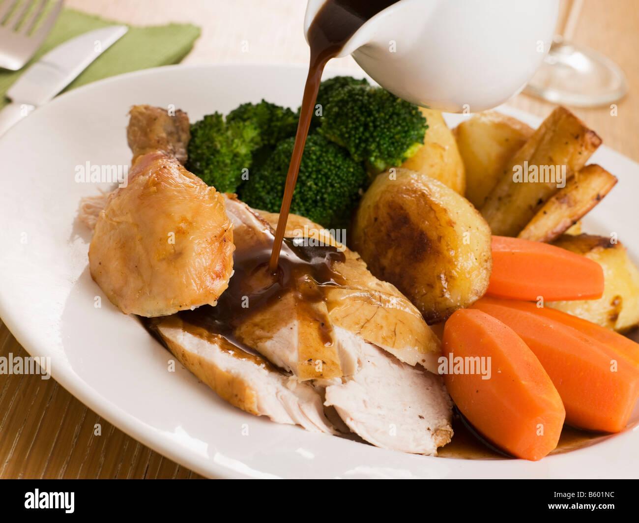 On verse la sauce sur une assiette de poulet rôti Photo Stock