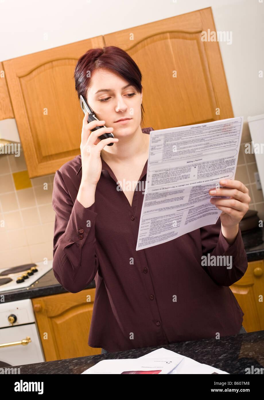 Jeune femme au foyer de payer ou de l'interrogation d'un projet de loi à l'aide de son téléphone Photo Stock
