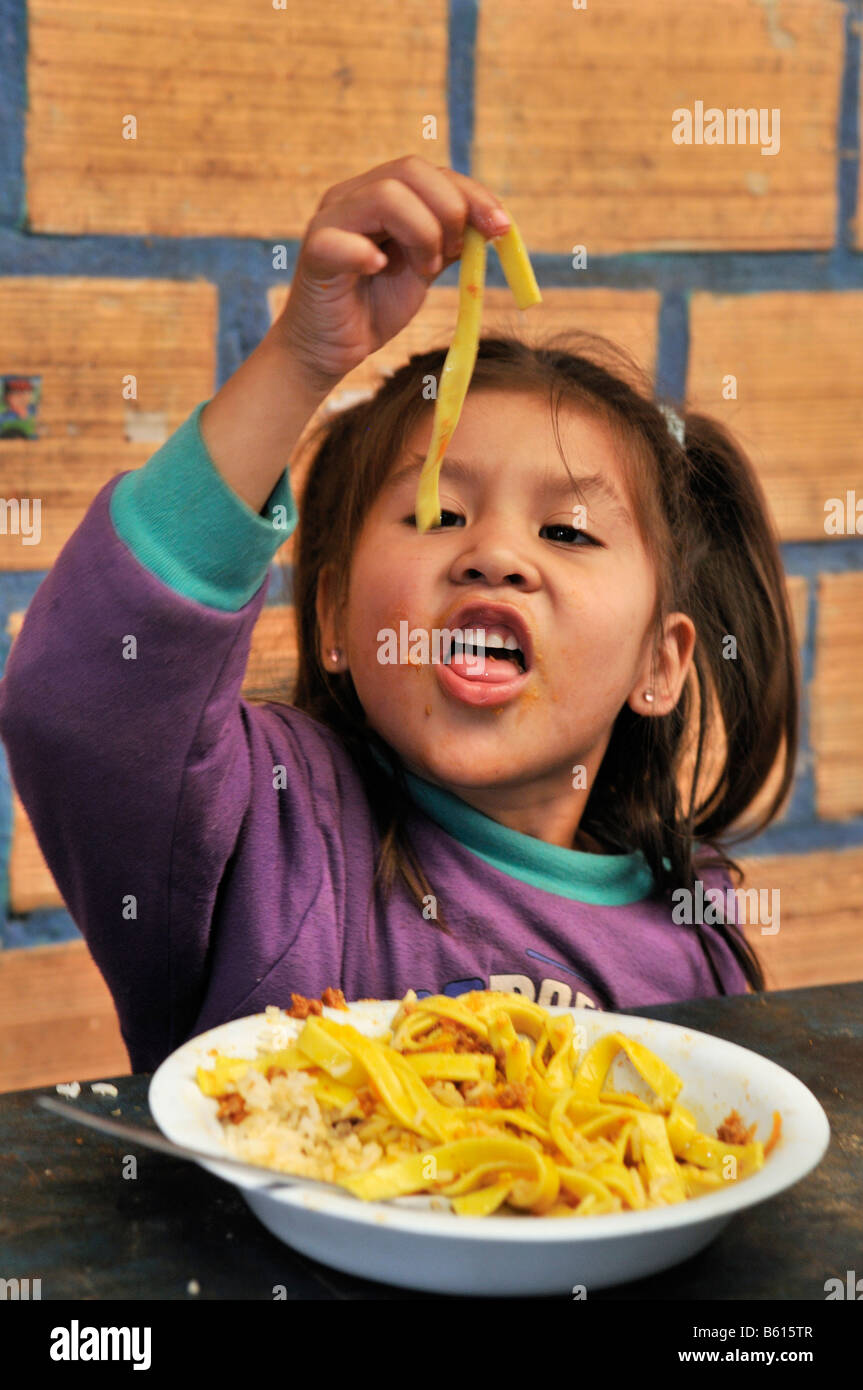 Girl eating noodles ruban avec ses doigts, bidonville Plan 3000, Santa Cruz, Bolivie, Amérique du Sud Photo Stock