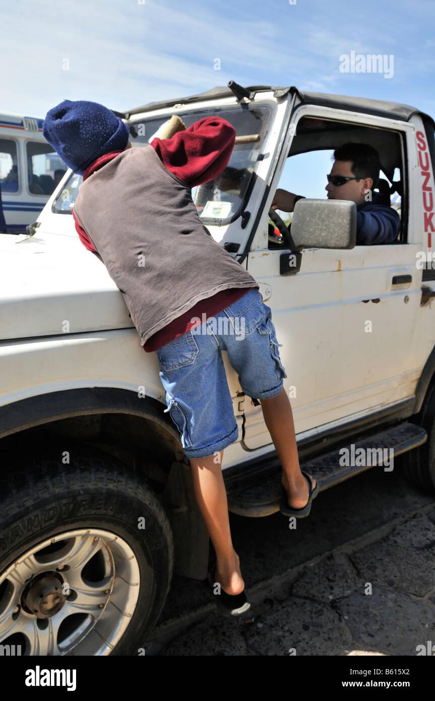 Garçon de quinze ans le nettoyage des vitres de voitures à une intersection, Santa Cruz, Bolivie, Amérique Photo Stock