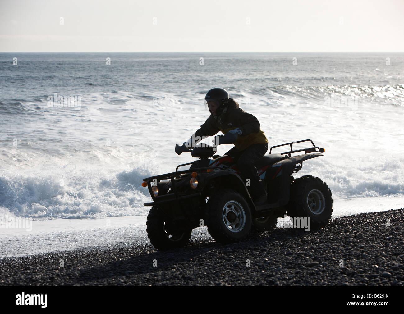 Girl riding Quad sur sable noir plage rocheuse, Hornafjordur, fjord Islande de l'Est Banque D'Images