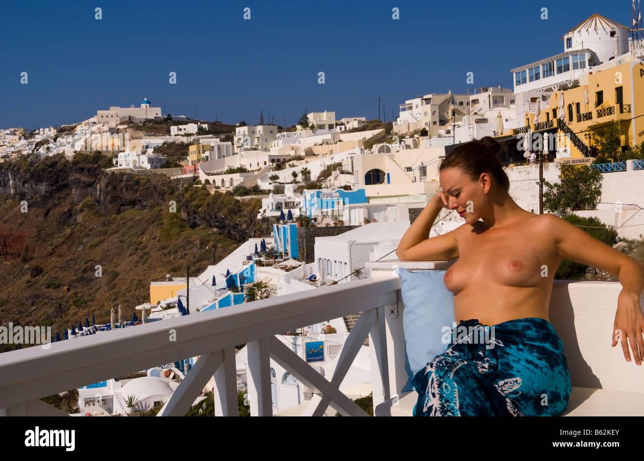 bâtiments les Fira à topless de sur porche falaises les Grèce blancs Jeune 20s femme Santorin sur le de séduisante donnant sur Tqp6vB