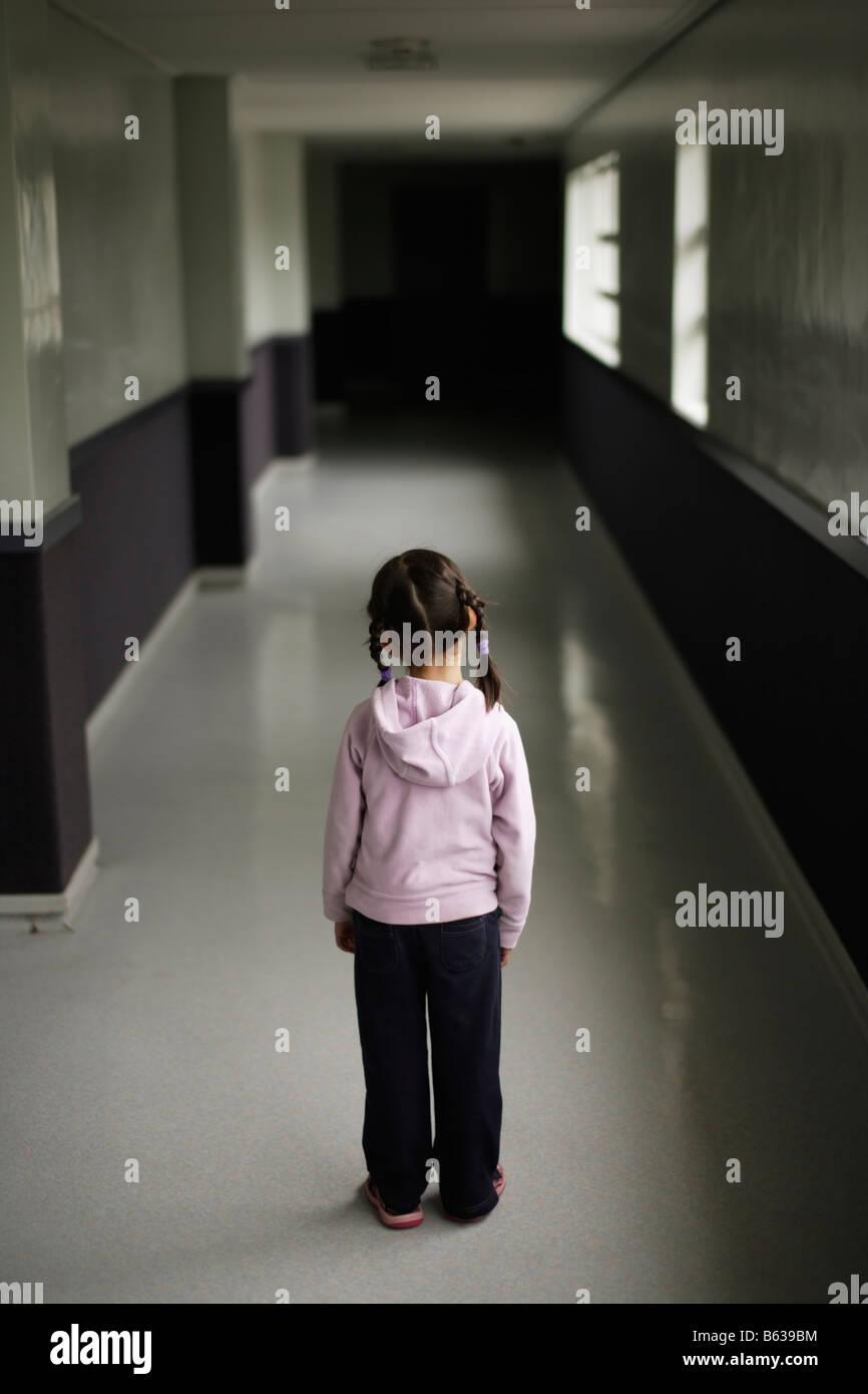 Petite fille de cinq ans est le seul à l'école corricor Banque D'Images