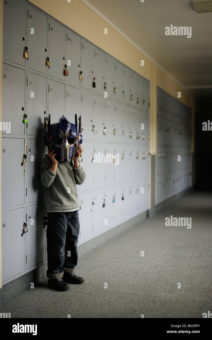 Boy in school corridor portant masque robot Transformateur Banque D'Images