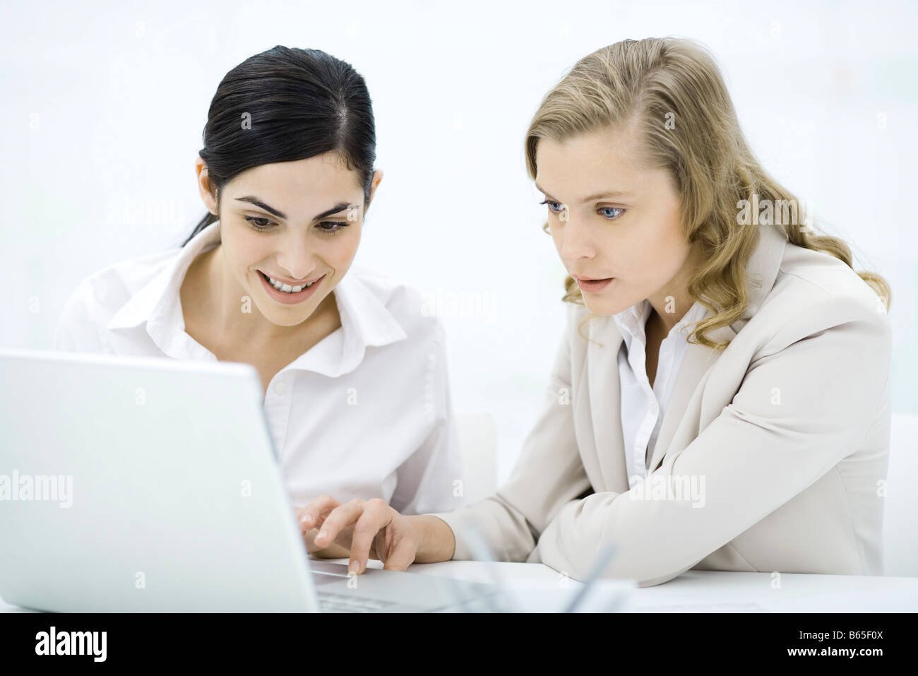 Professional women looking at laptop computer together, smiling Photo Stock