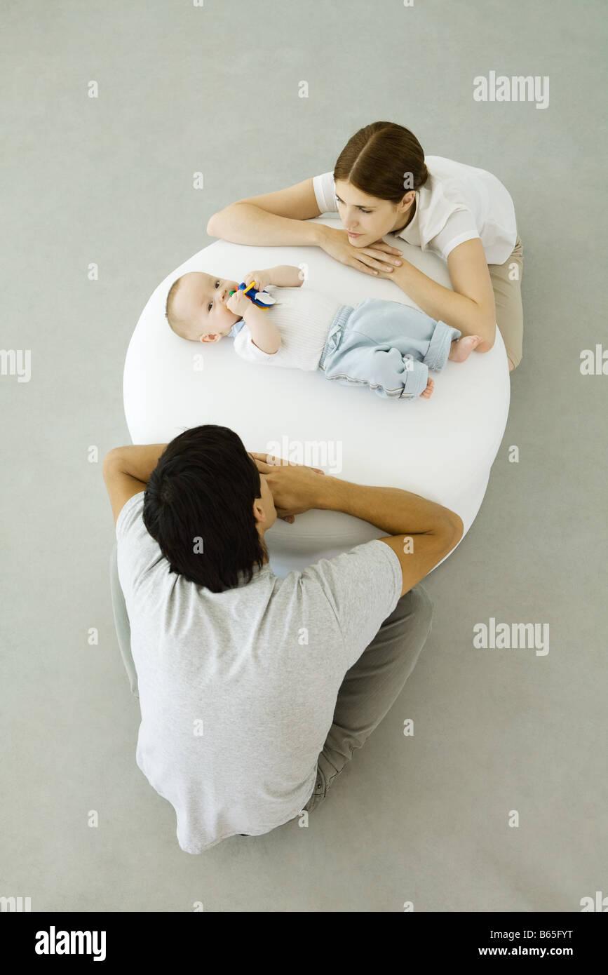 Les jeunes parents appuyé contre un pouf, regardant bébé couché entre eux Banque D'Images