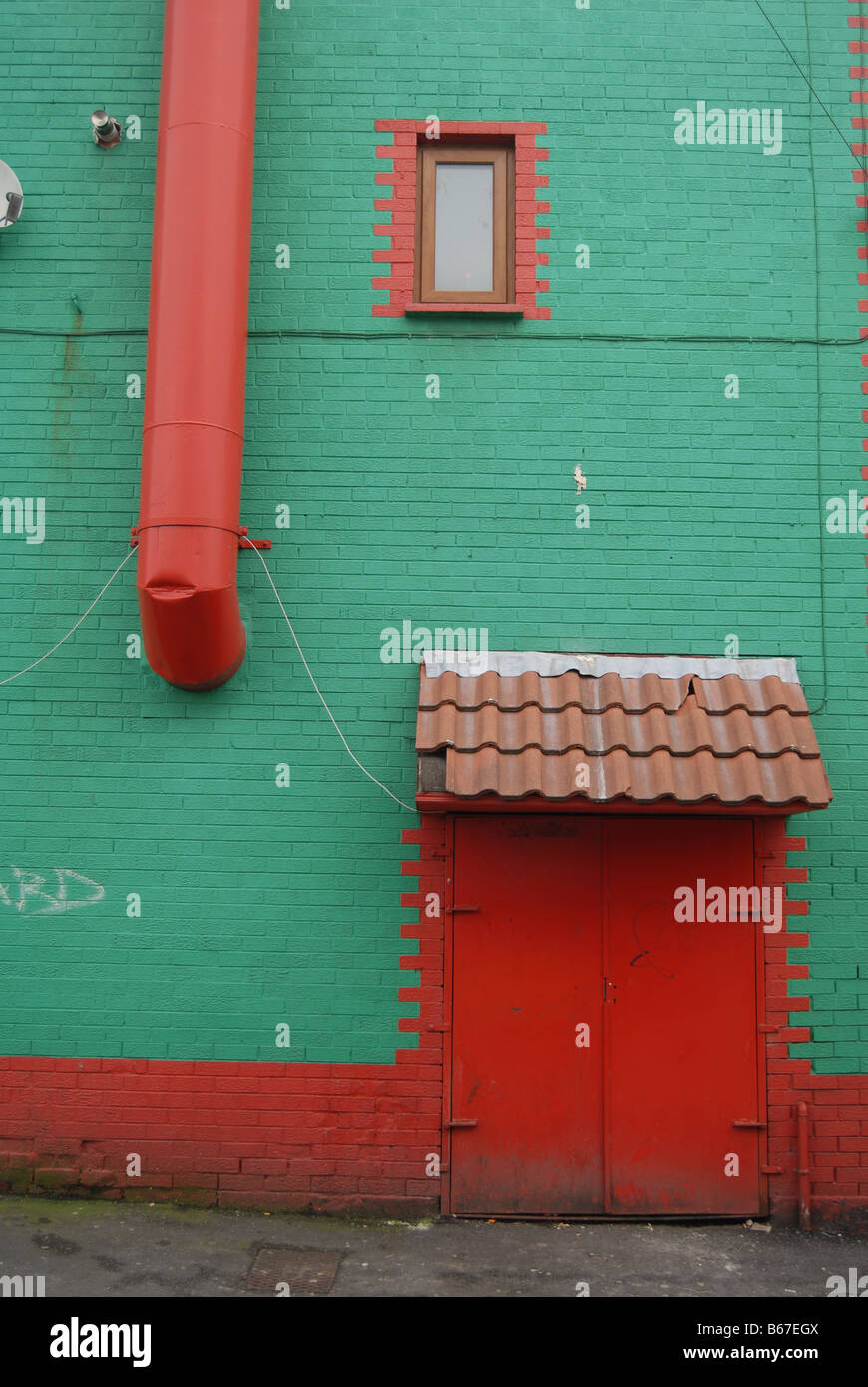 Une porte arrière peint en rouge situé dans un mur de couleur vert profond forme une composition , East Photo Stock