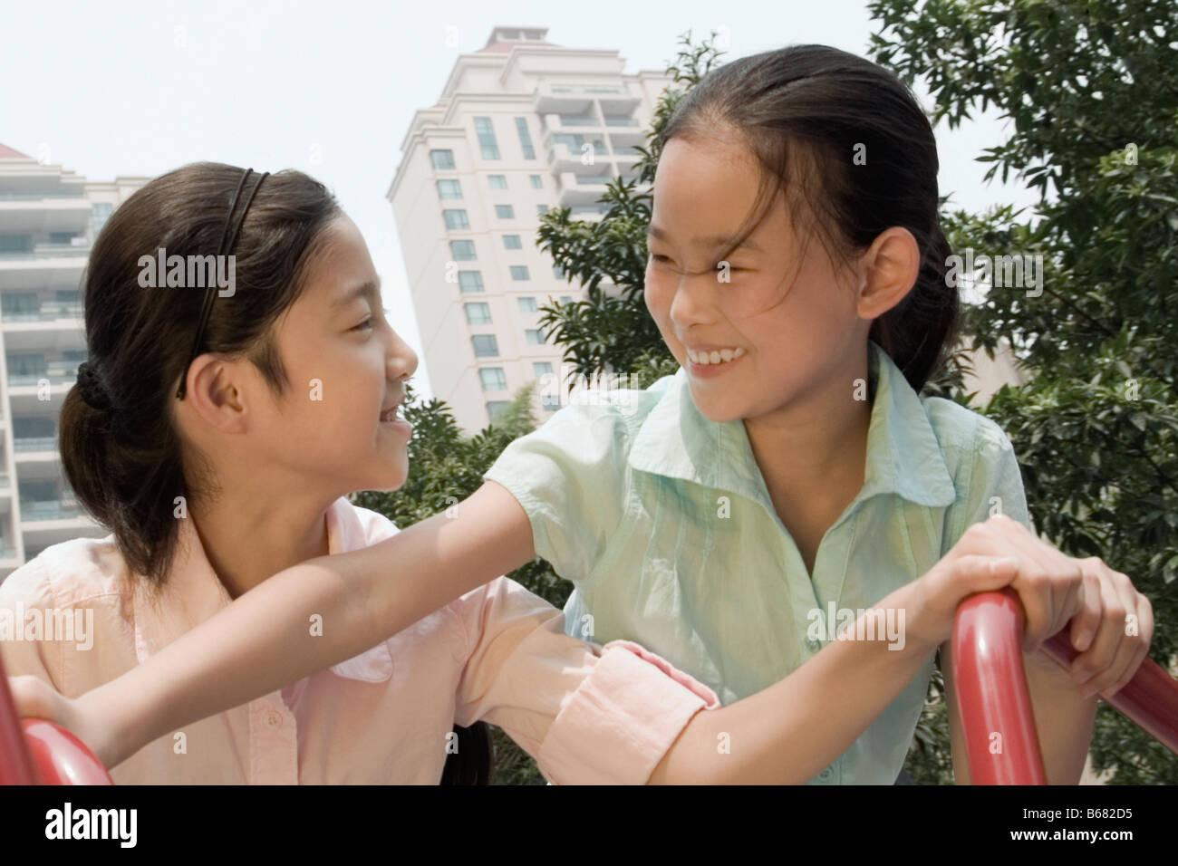 Jeune fille et sa sœur jouant sur un manège Photo Stock