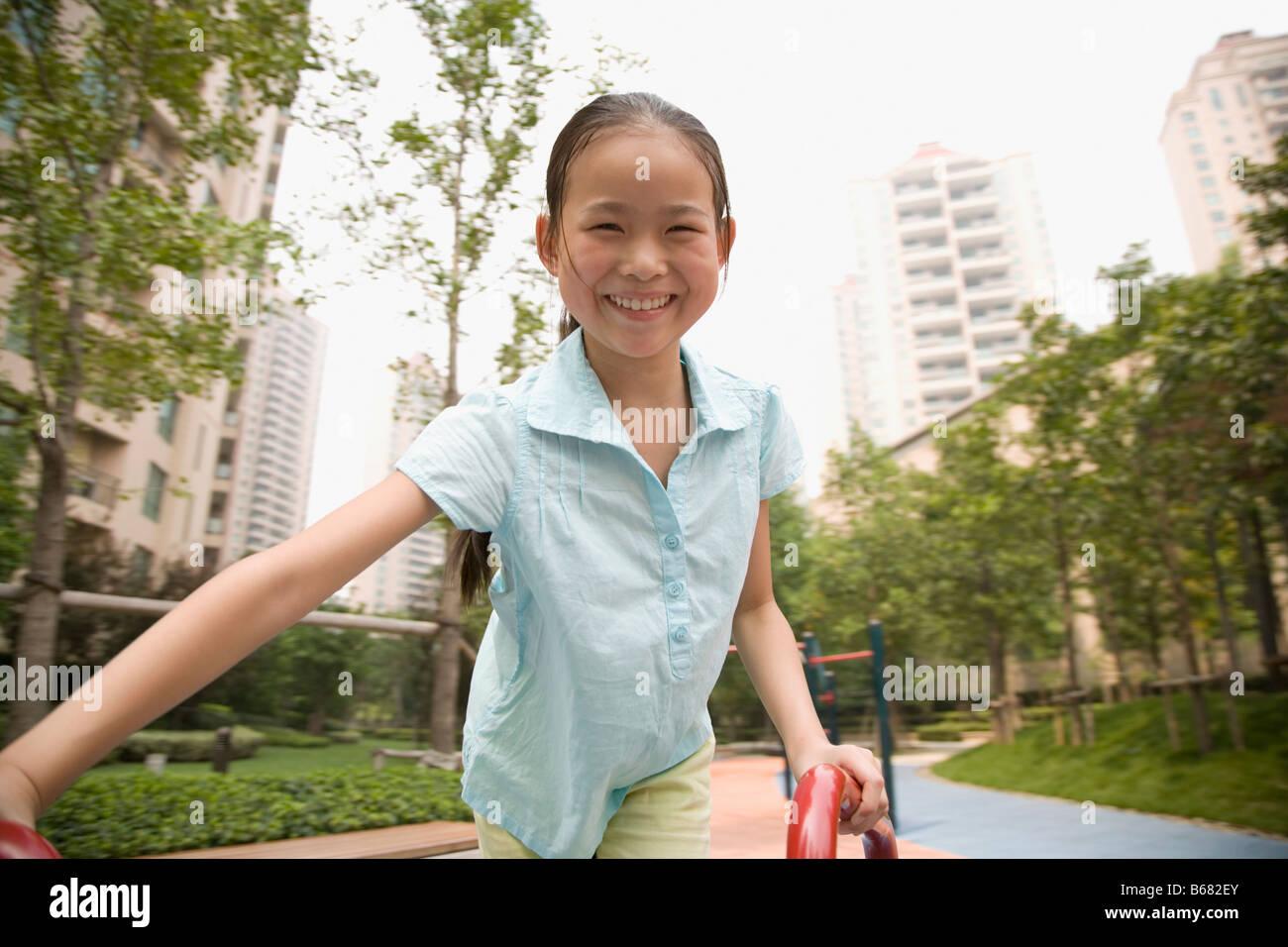 Portrait d'une jeune fille jouant sur un manège et souriant Photo Stock