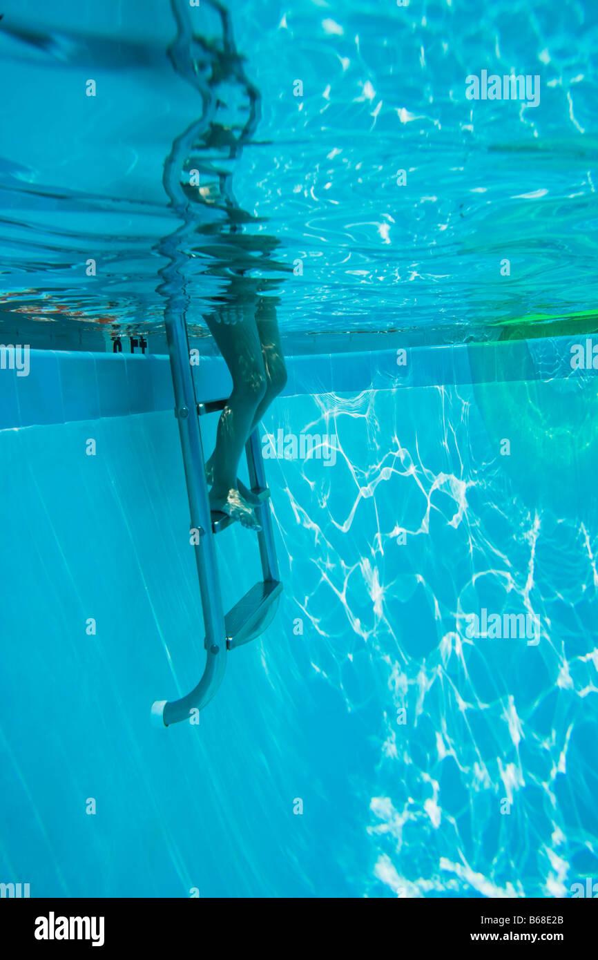 Les jambes sur l'escabeau en piscine Photo Stock