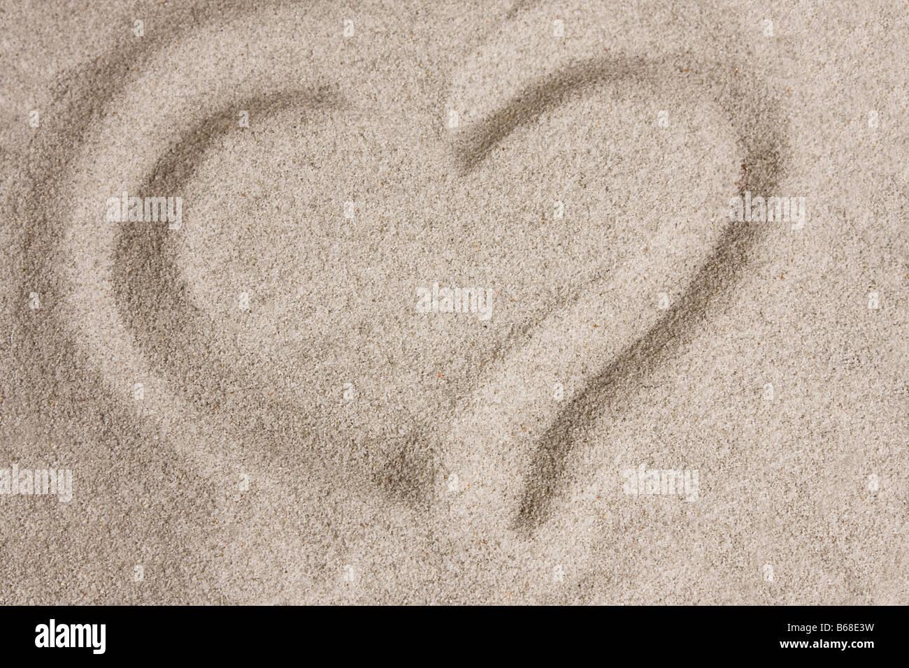 Coeur de la forme écrite dans le sable Photo Stock
