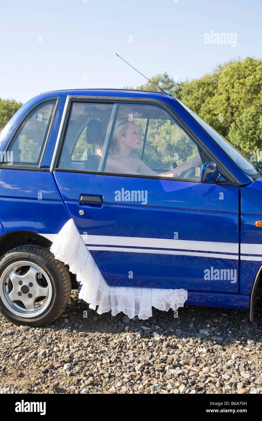Jeune femme à la roue de la voiture électrique Photo Stock