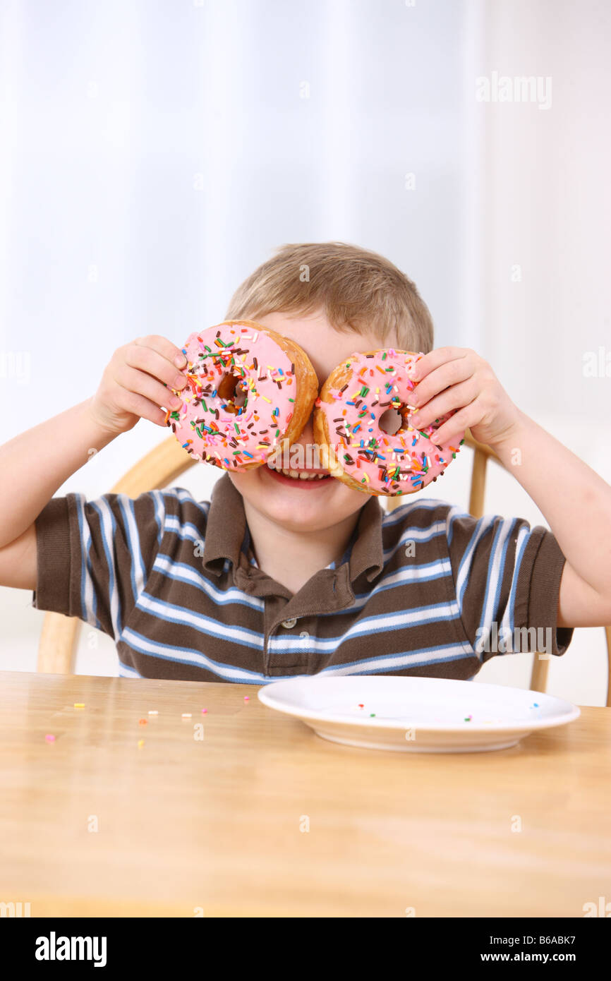 Young boy holding donuts au-dessus des yeux Photo Stock
