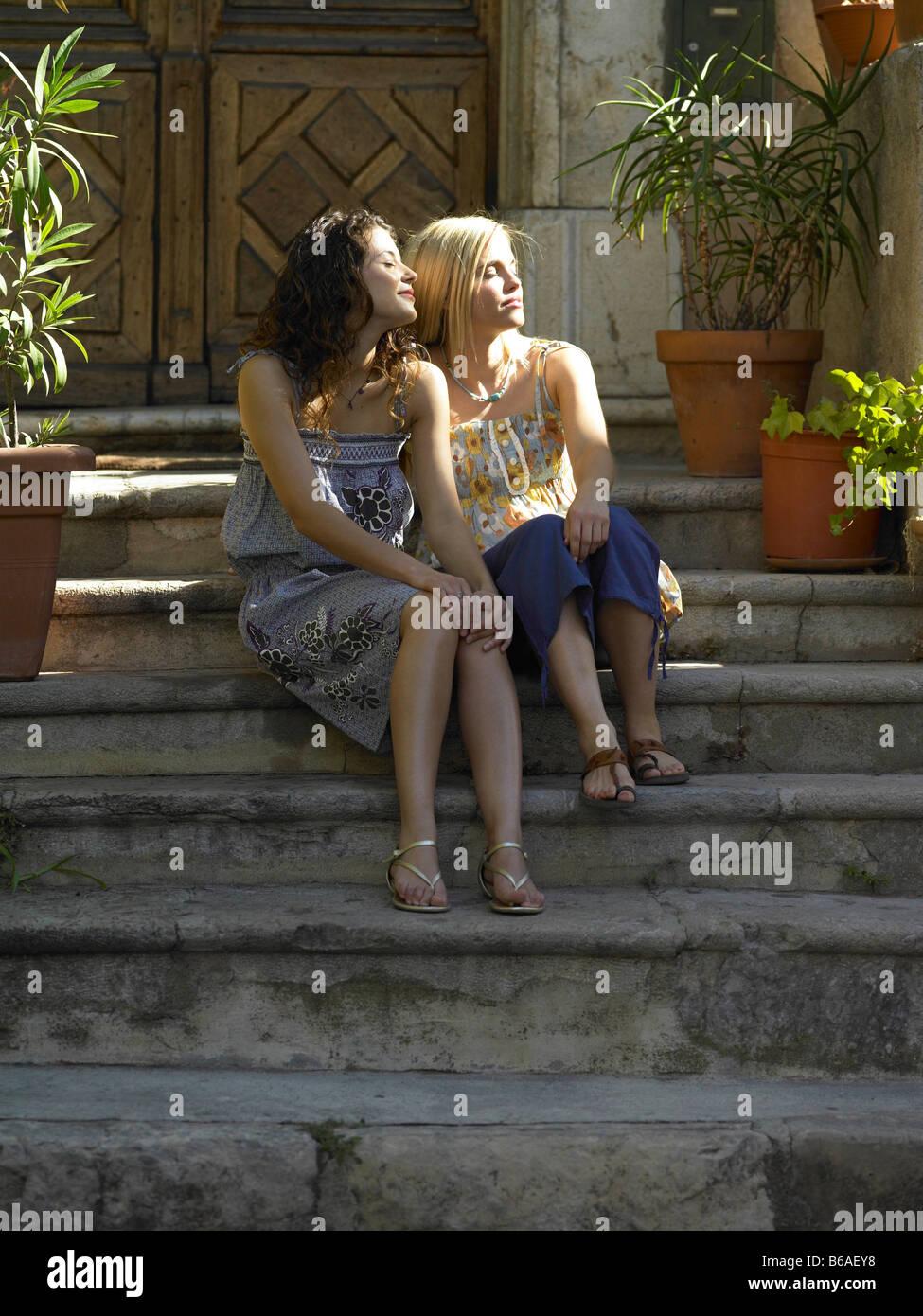 Amis féminins assis sur l'étape Photo Stock