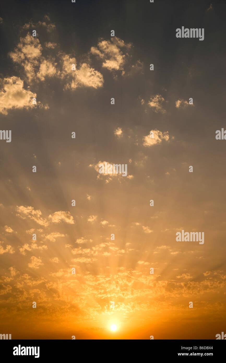 Des rayons de lumière SOLEIL CLOUDSCAPE RÉTROÉCLAIRÉ PAR PUFFY NUAGES SUR CIEL JAUNE Photo Stock