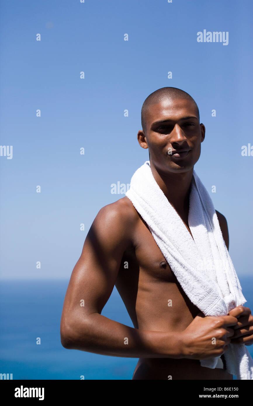 L'homme en vacances avec une serviette autour de ses épaules. Il a vingt ans. Photo Stock