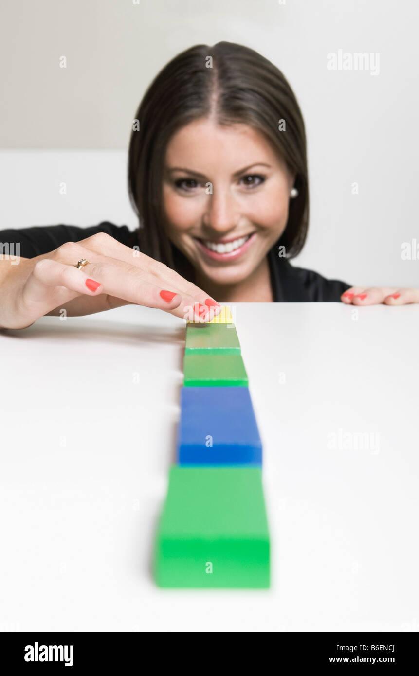Femme plaçant des blocs dans une rangée Photo Stock
