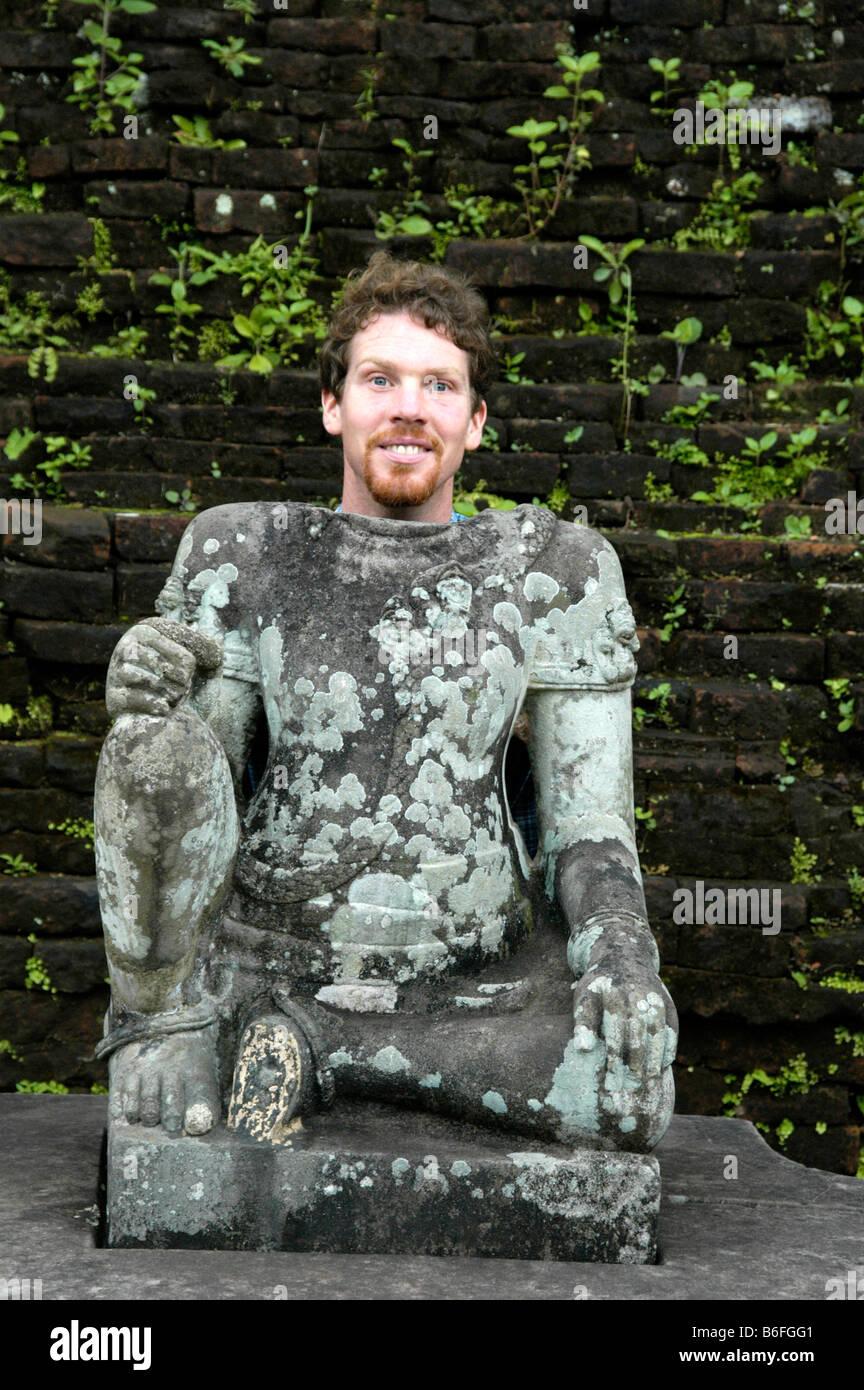 Homme debout derrière statue sans tête dans le temple de la Cham du groupe B et C, mon fils, au Vietnam, Photo Stock
