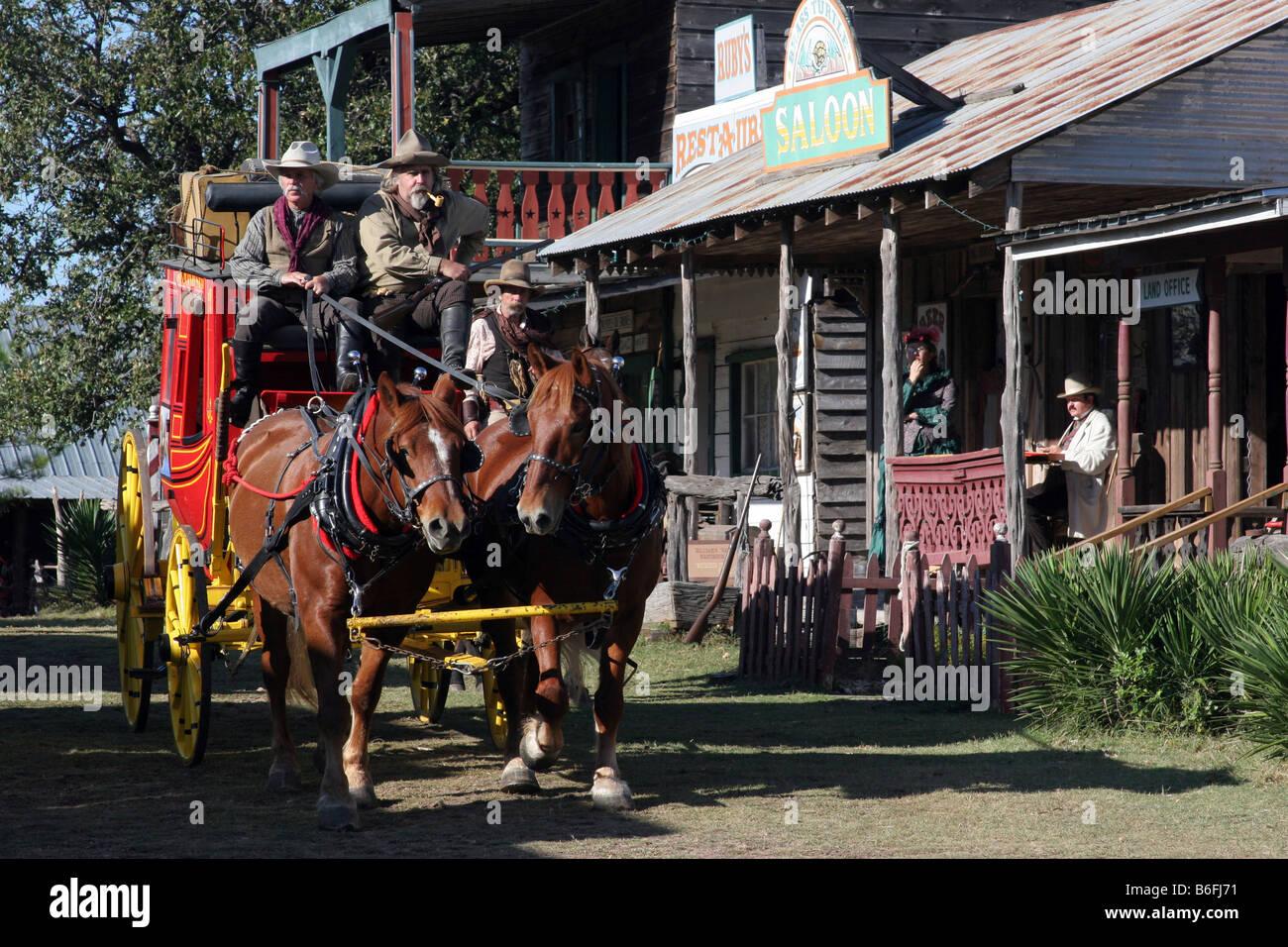 Deux cowboys conduisant le Butterfield Overland Stage Coach à travers une vieille ville de l'ouest Banque D'Images
