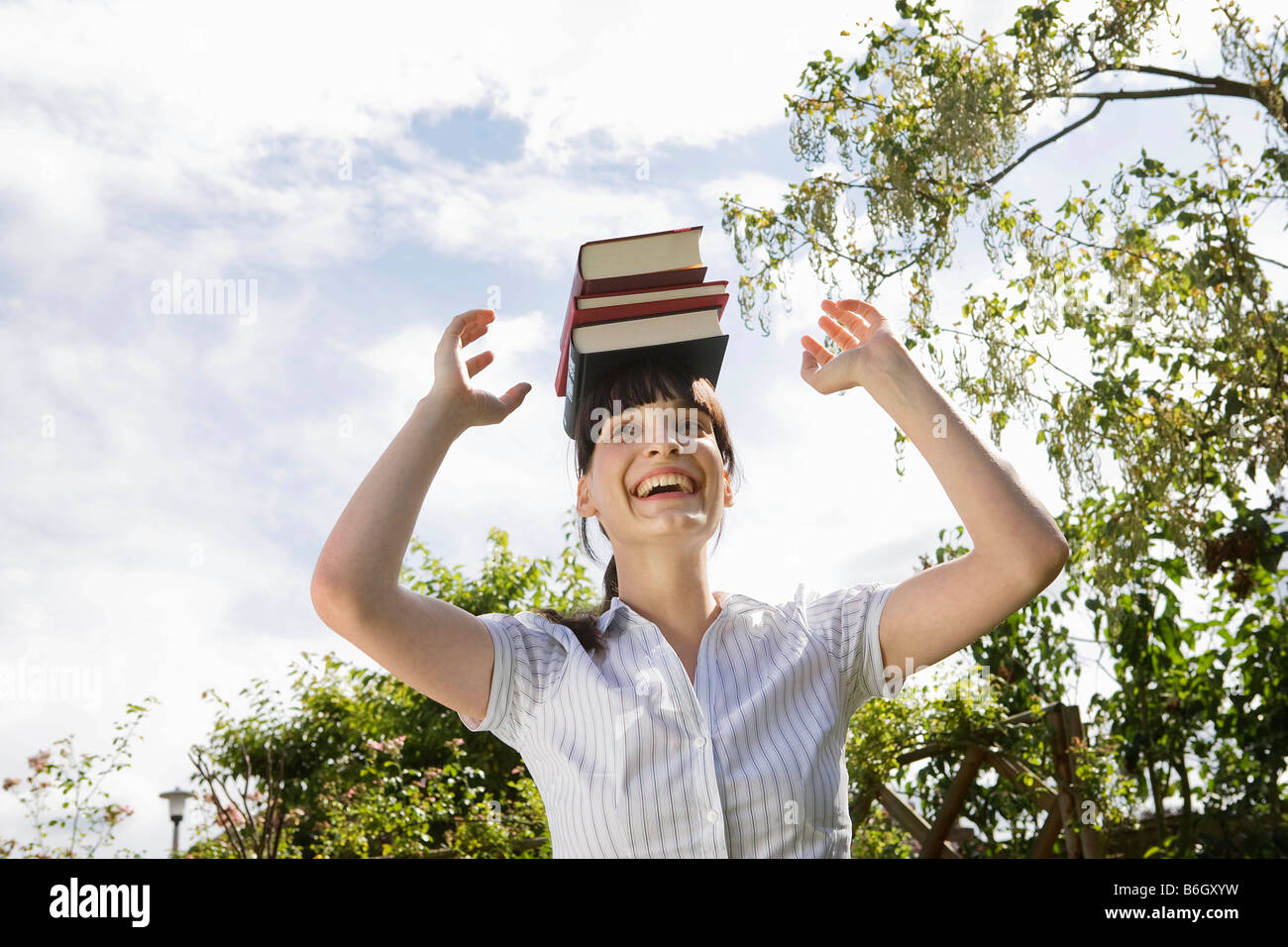 Woman balancing books on head, rire Banque D'Images
