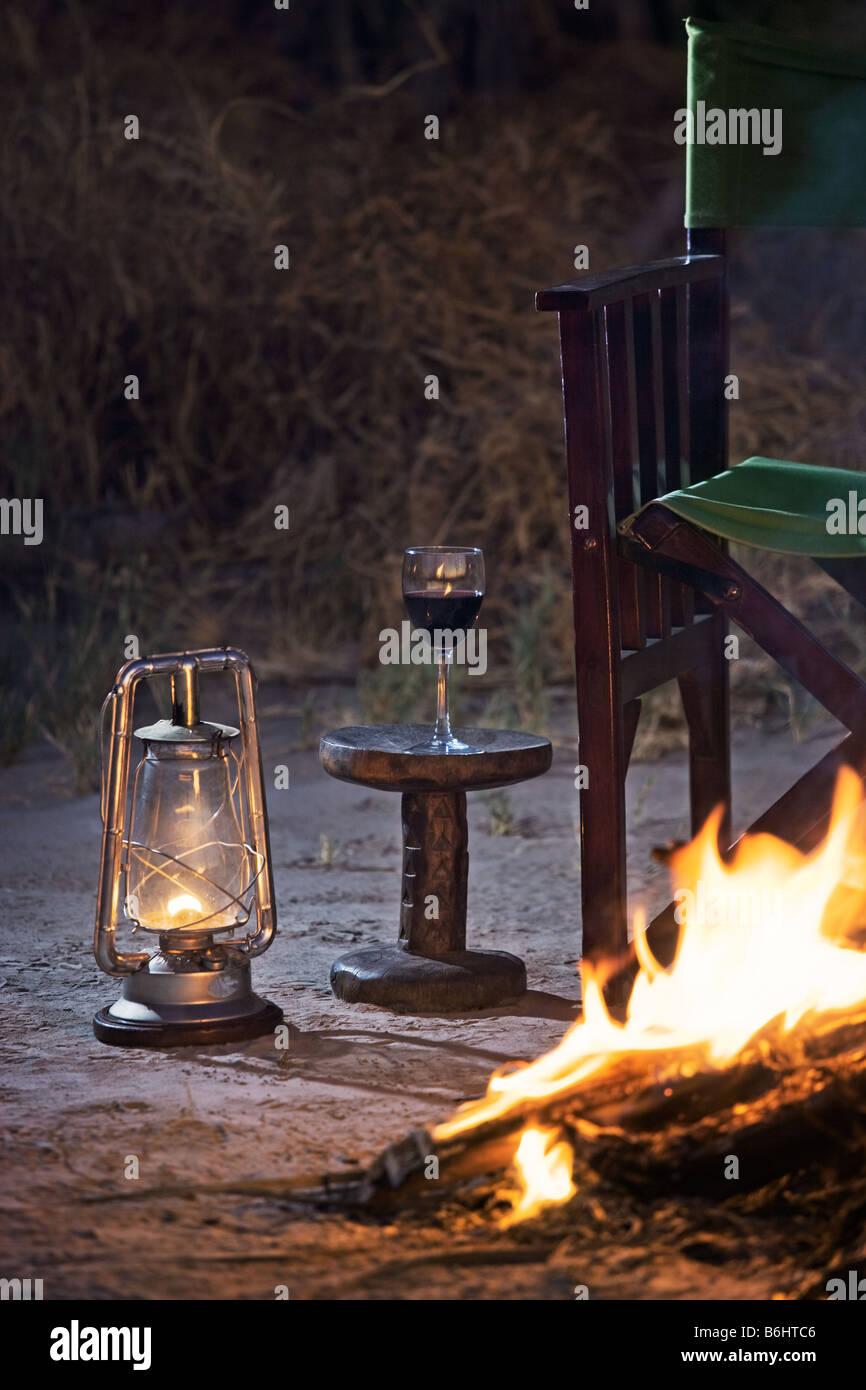 Détente à un feu de camp avec un verre de vin rouge Jack's Camp Makgadikgadi Pans, Botswana Banque D'Images
