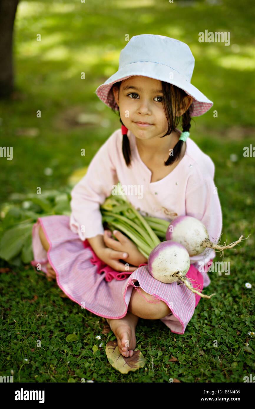 Petite fille de cinq ans tient deux navets cultivés bio Photo Stock