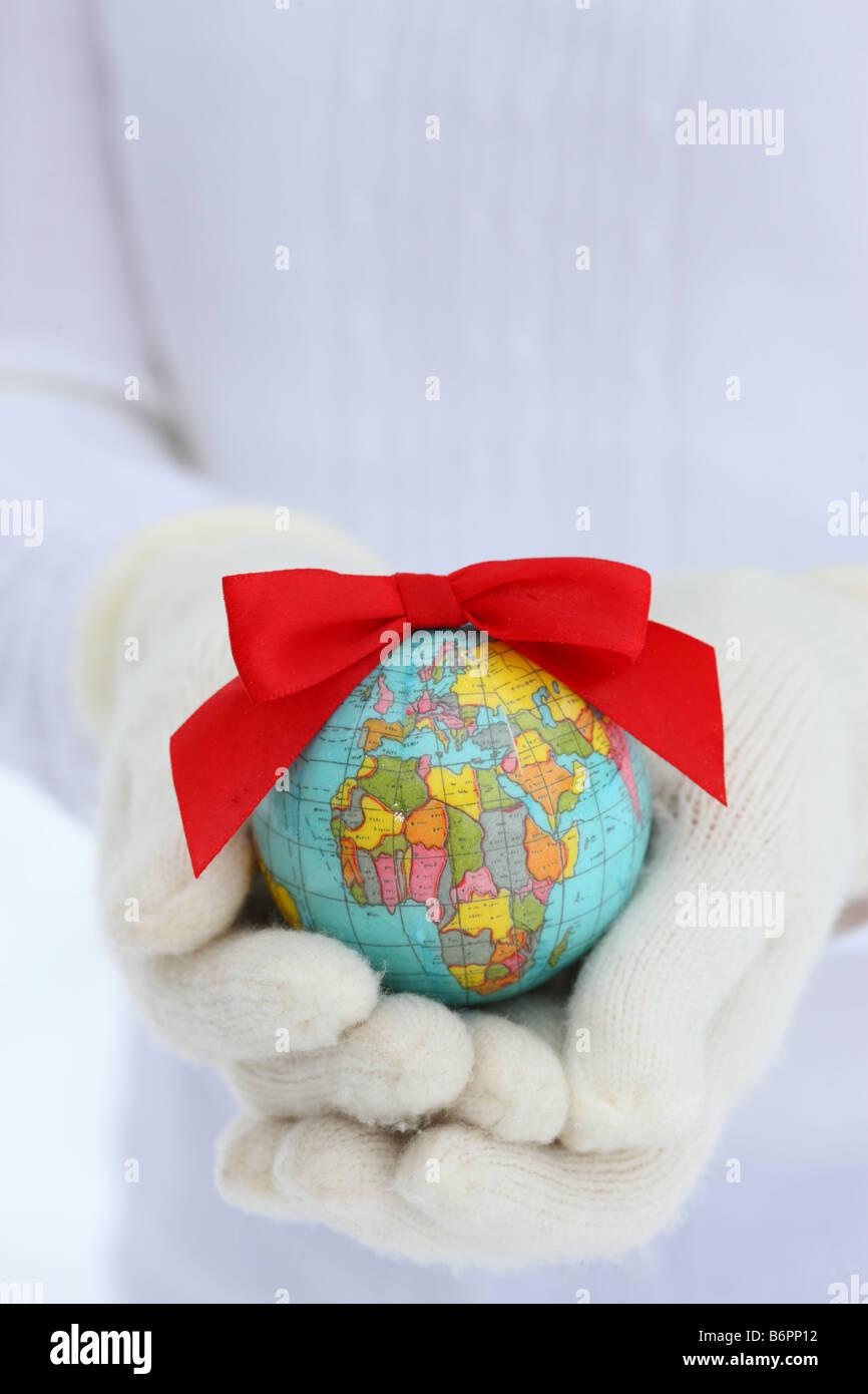 Les mains avec des gants hiver holding Earth avec Christmas bow Photo Stock