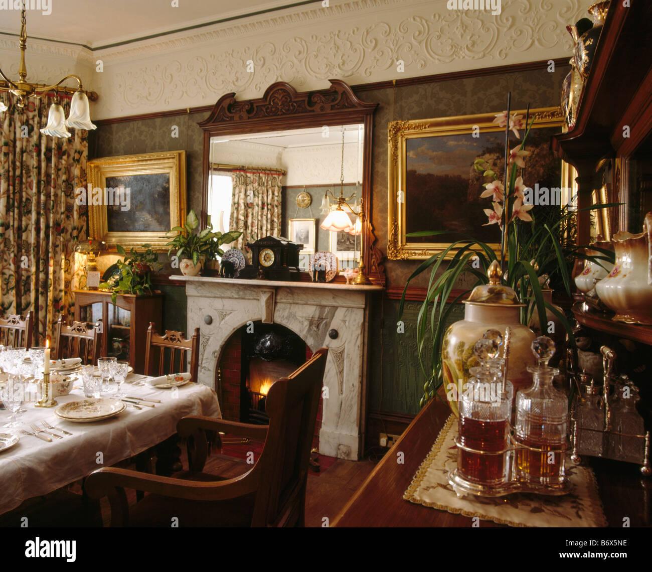 miroir au dessus de chemine dans la salle manger victorienne avec des images encadres de dorures et de stucs ornementaux corniche