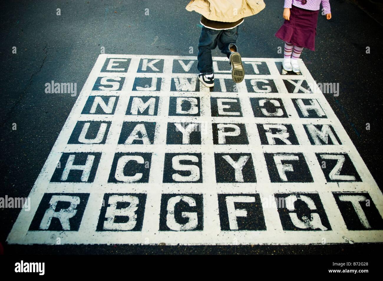 Les enfants jouent sur un jeu de l'alphabet d'asphalte dans la cour de l'école. Photo Stock