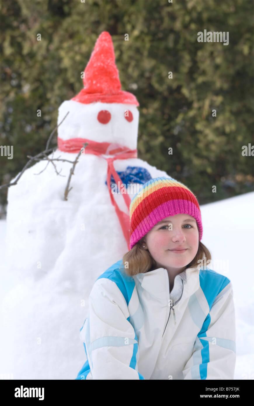Treize ans, fille agenouillée à côté de snowman, Winnipeg, Canada Photo Stock