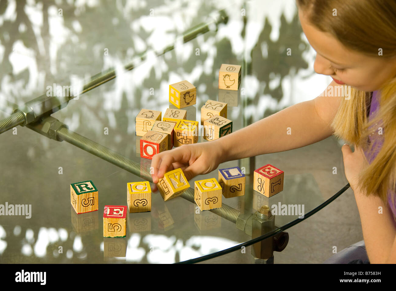 Jeune fille orthographe recycle avec alphabet blocks Photo Stock