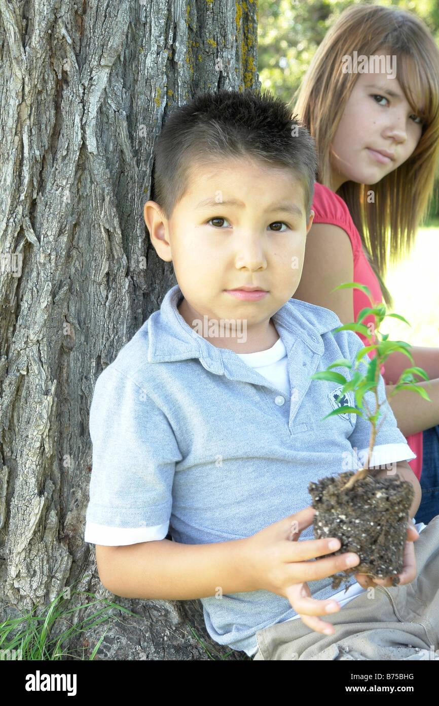 13 ans, fille et garçon de six ans avec petit arbre assis à côté d'arbre, Winnipeg, Canada Banque D'Images