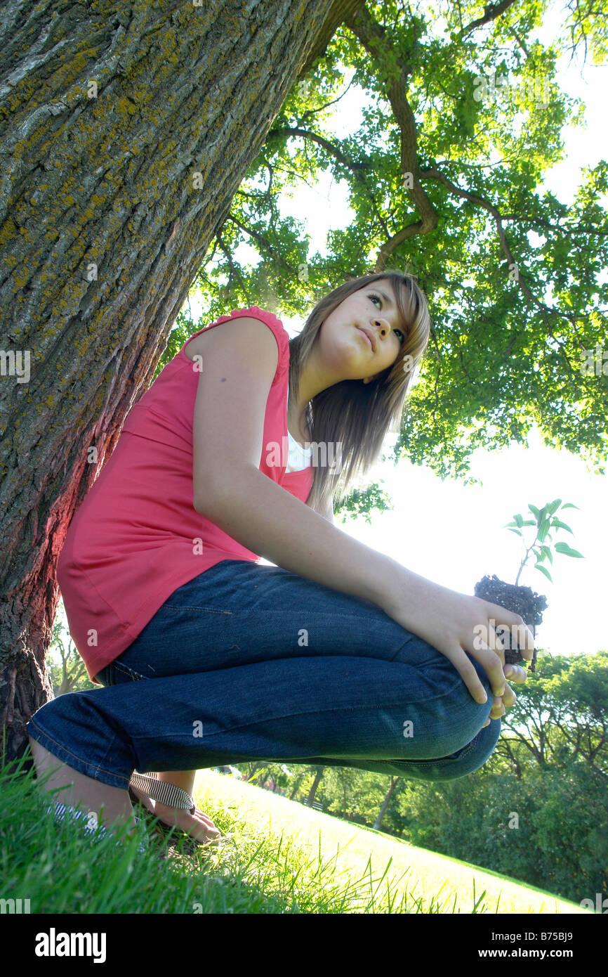 Treize ans girl holding petit arbre accroupis à côté d'arbre de plus grande taille, Winnipeg, Photo Stock