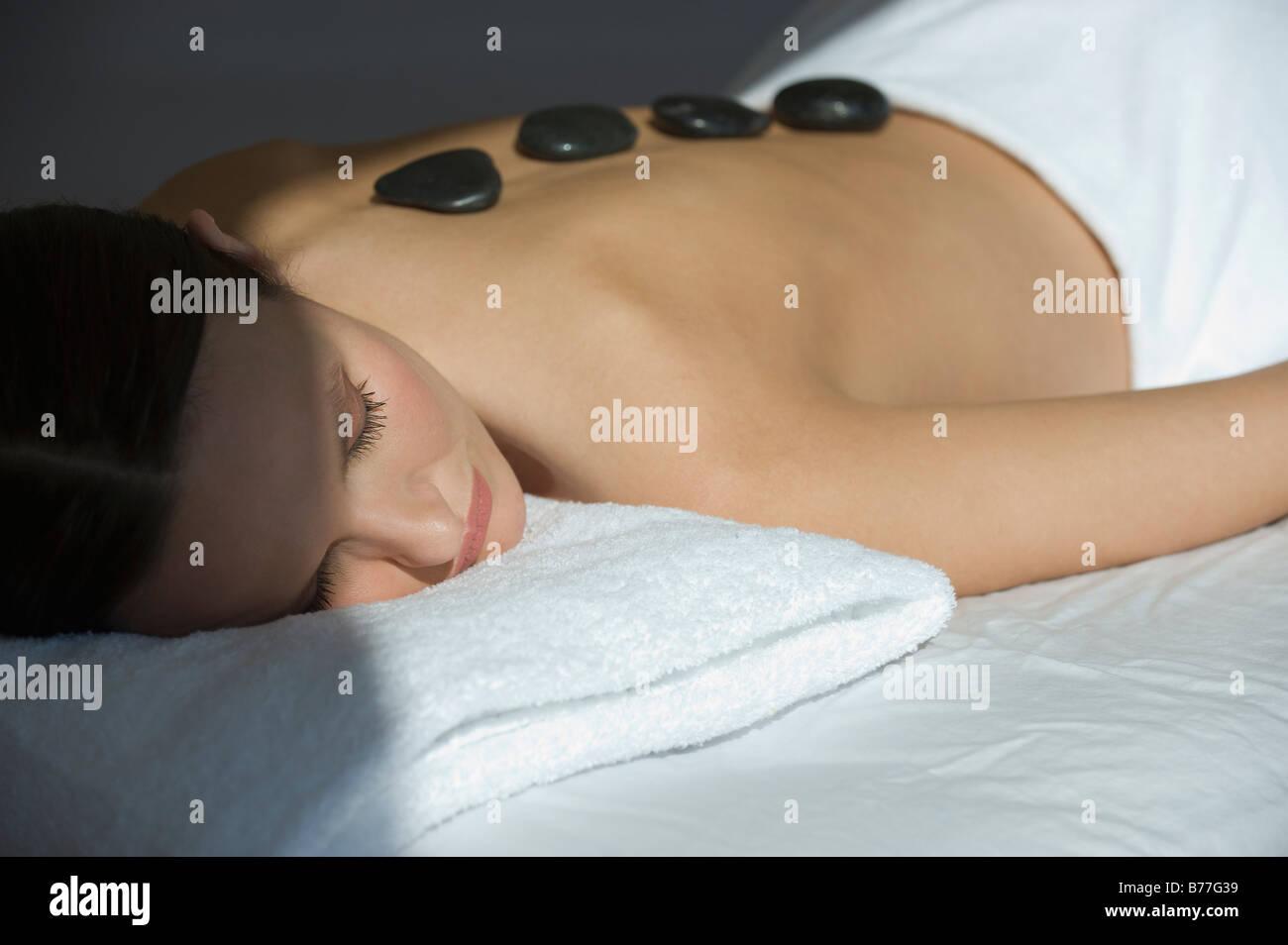 Femme portant sur table de massage pierres chaudes sur le dos Banque D'Images