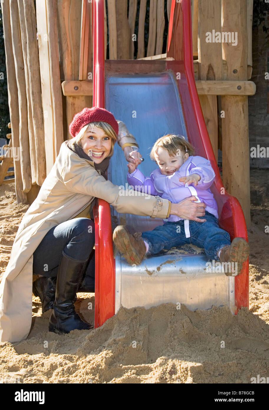 Mère et sa fille de 2 ans sur une diapositive, aire de jeux, Zurich, Switzerland, Europe Banque D'Images