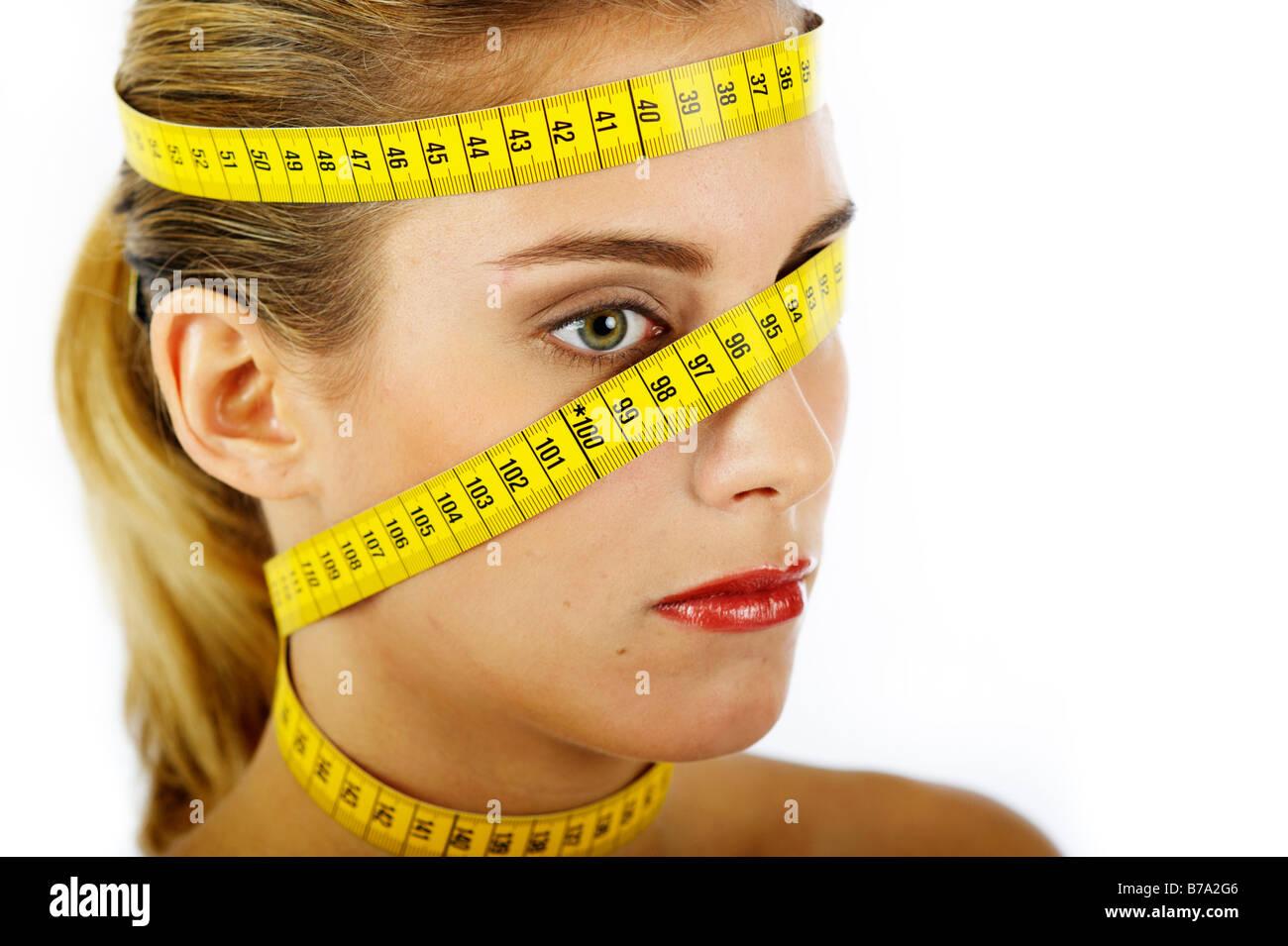 Jeune femme avec mètre à ruban enroulé autour de la tête et du cou Photo Stock