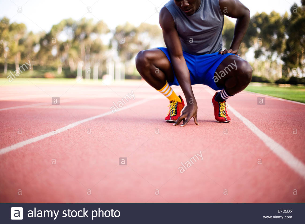 African American runner accroupis sur la voie Photo Stock