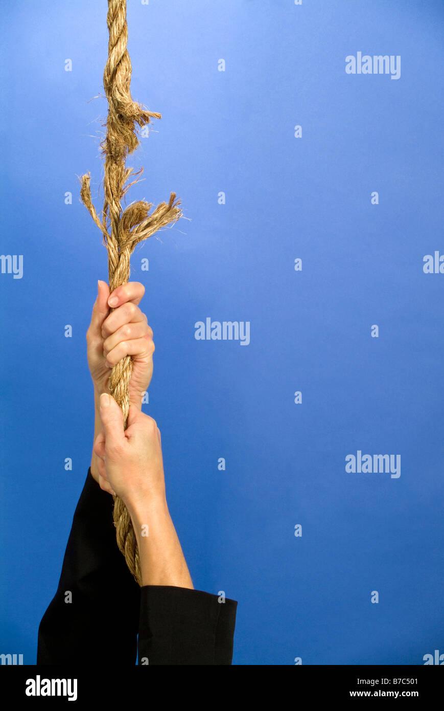 Une personne s'accrocher à une corde qui est effilochée et sur le point de rompre Photo Stock